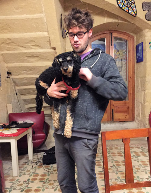 Guy holding black and tan traveller-dog in Maltese coworking space