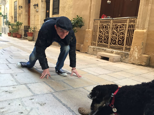 Dog playing with happy guy on a Malta street