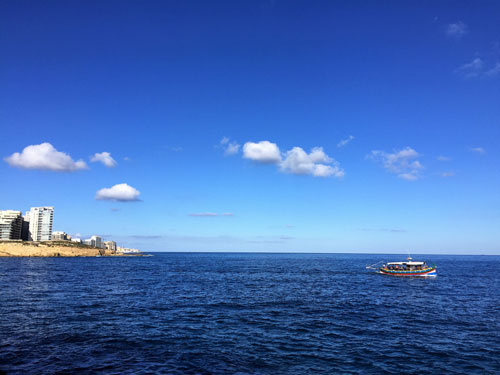 Blue sea, blue sky and a boat when discovering the Maltese coast