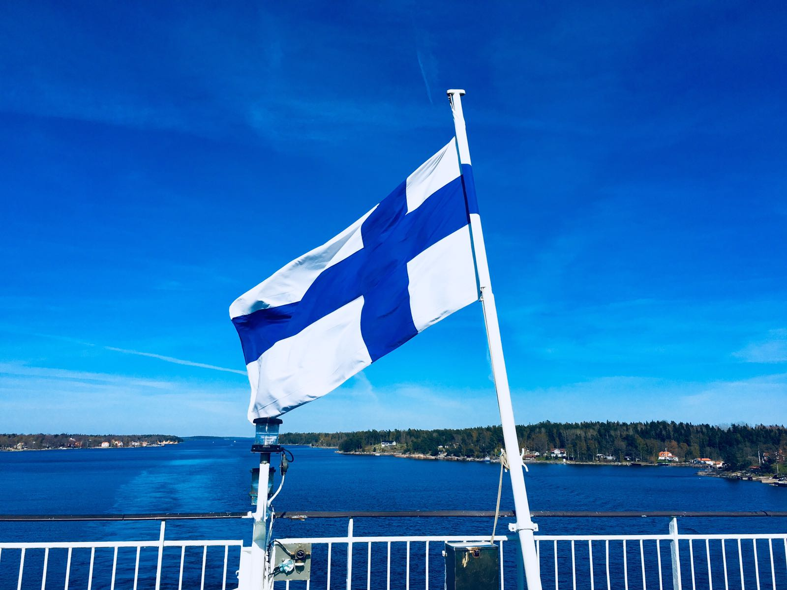 Finnish flag on back of a boat. Beautiful weather, blue skies