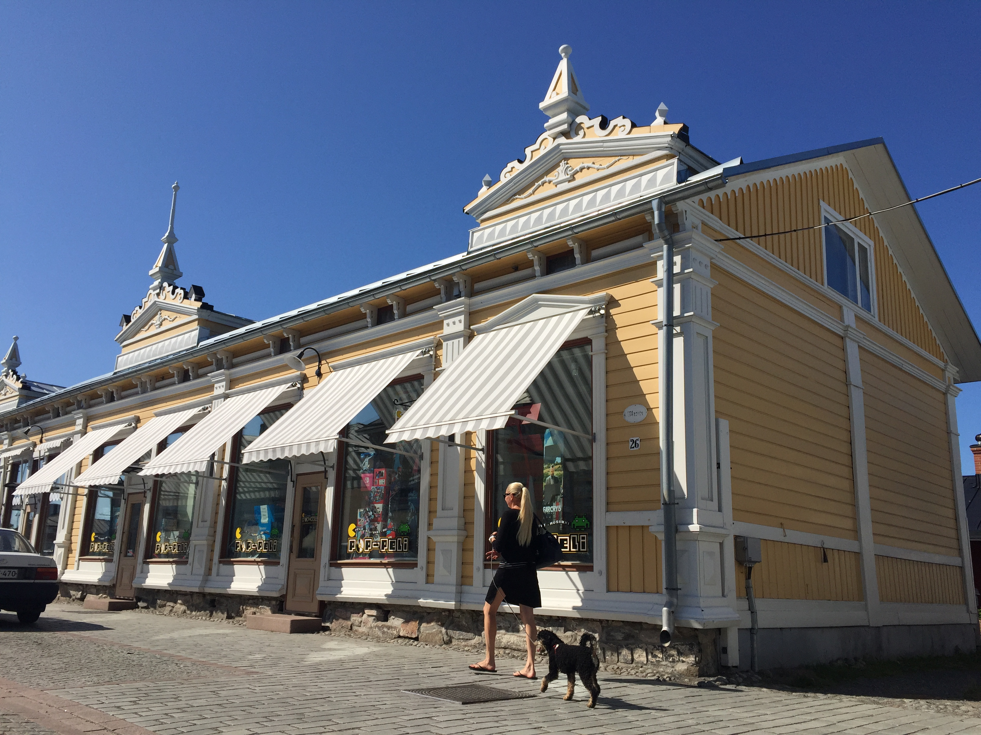 Yellow historic wooden building and dog in Finland