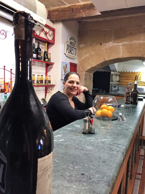 Smiling Sicilian bar-tender in quaint reststaurant