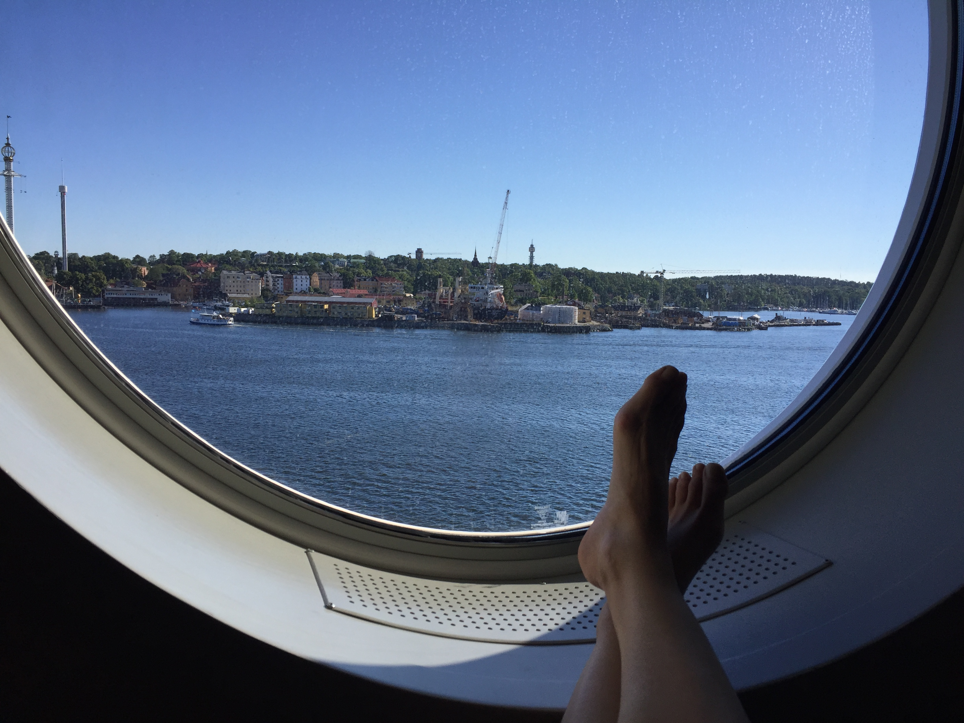 Someone relaxing in front of round window on Finnish cruise ship