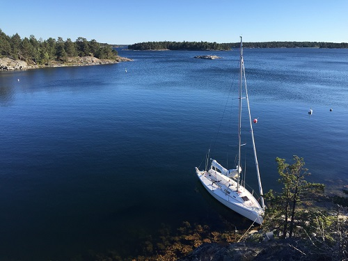 White sailboat on bright blue water in Swedish archipelago
