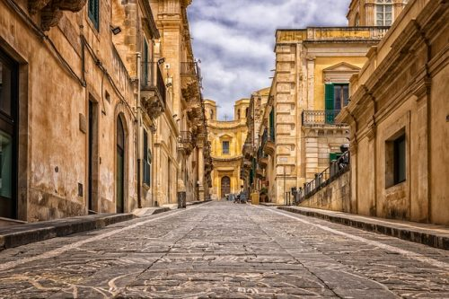 Cobble stone street in Sicily lined with old historic buildings