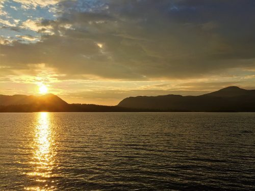The sun is settin over a big lake in Elgå, Norway. The mountains behind the lake are soft and rolling.