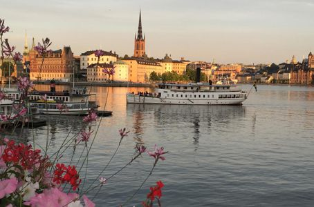 Sunset over old town of Stockholm and a ferry boat