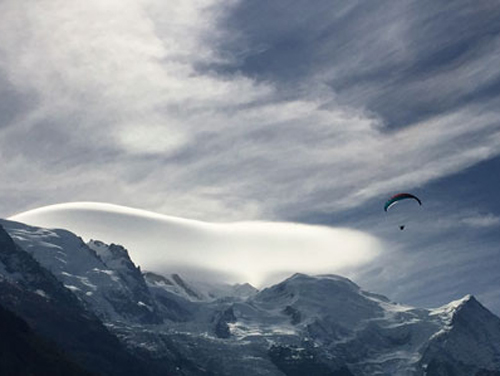 View of snowy mountains and paraglider when dog hiking in French Alps