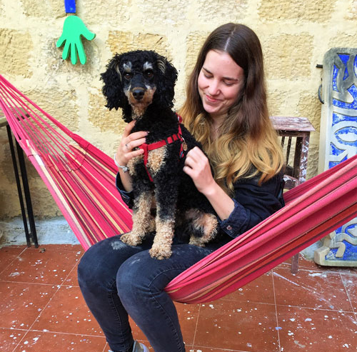 Happy girl and cute dog in a red hammock in Malta