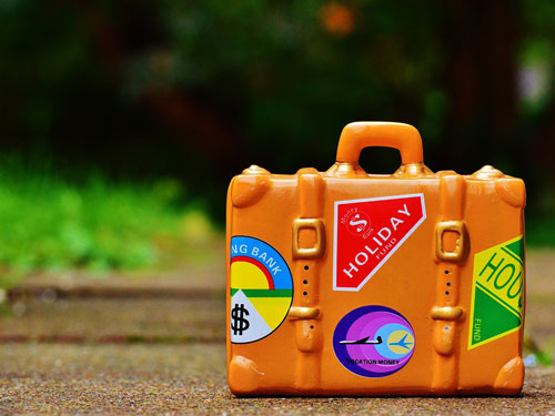 Orange suitcase with travel-stickers on it
