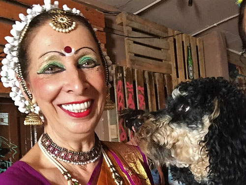 Travelling dog looking at beautiful woman dressed in traditional Indian clothes