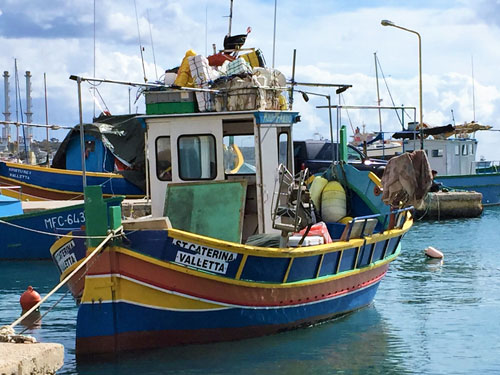 Colorful and overloaded fishing boat in Malta